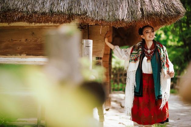 Charmant jong meisje in een gekleurde geborduurde jurk vormt in de buurt van het huis