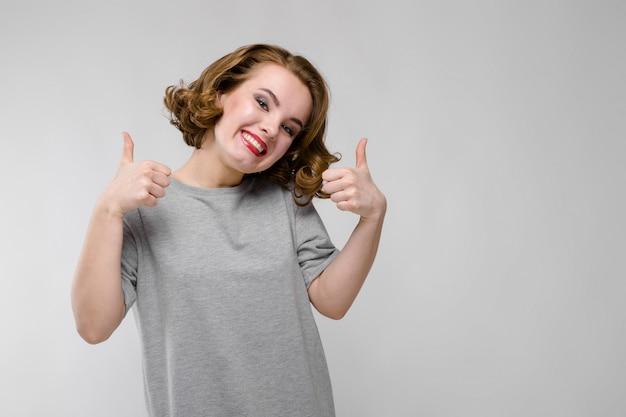 Charmant jong meisje in een grijs t-shirt. meisje klasse teken tonen