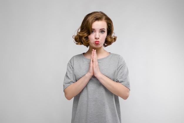 Charmant jong meisje in een grijze t-shirt op een grijs