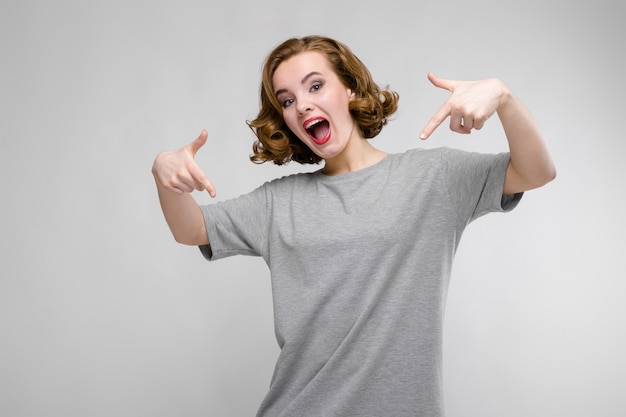 Charmant jong meisje in een grijze t-shirt op grijs