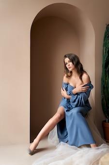 Charmant jong meisje met mooie make-up en kapsel dragen blauwe jurk, trendy oorbellen en hoge hakken, zittend op een stoel bedekt met witte lichte sluier. concept van schoonheid en sensualiteit