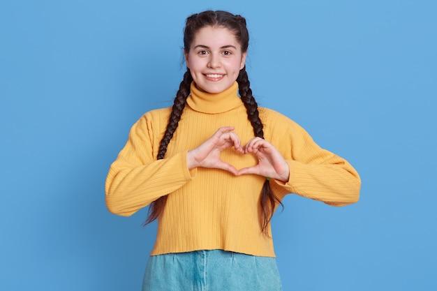 Charmant jong meisje toont liefde, toont hartgebaar, glimlacht breed, heeft romantische gevoelens, voelt geluk, gekleed in casual felgele trui en spijkerbroek