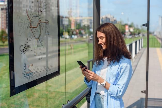 Charmant jong meisje volgt de bus via een mobiele app terwijl ze 's ochtends bij een halte van het openbaar vervoer staat.