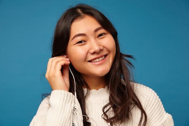 Charmant jong positief aziatisch wijfje dat met golvend kapsel oortelefoon opneemt