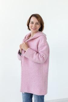 Charmant jong vrouwelijk model poseren op een witte muur in een designer roze jas. het concept van een uniek handwerkontwerp. advertentieruimte, copyspace