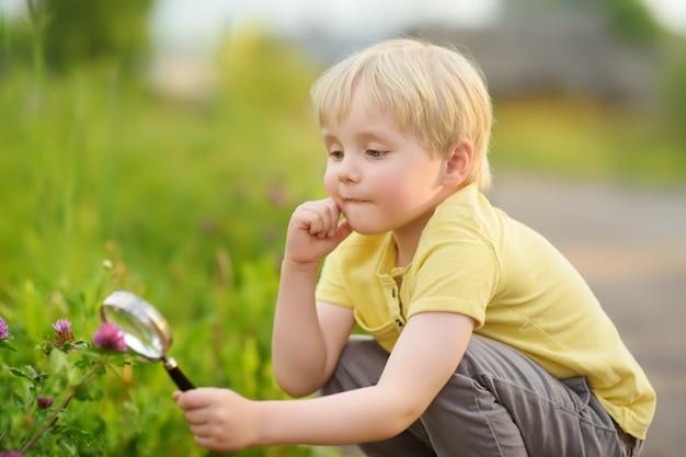 Charmant kind dat de natuur met vergrootglas onderzoekt