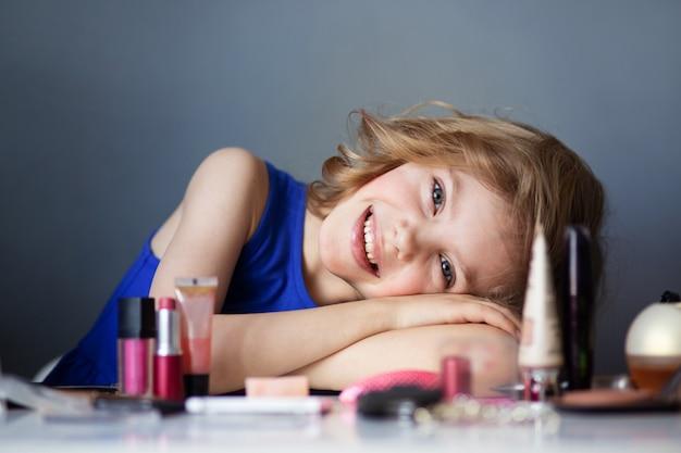 Charmant kind, kleine schoonheid, schattig meisje van 7-8 jaar oud met mooie blonde krullen, make-up, mama's make-up aan tafel, grijze muur