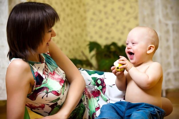 Charmant kind met grote blauwe ogen in blauwe broek zit op de vloer, houdt appel in zijn handen en kijkt naar moeder
