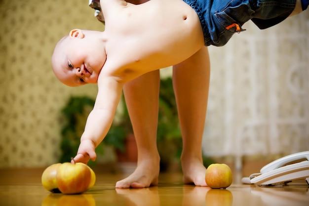 Charmant kind met grote blauwe ogen in blauwe broek zit op de vloer, houdt appel in zijn handen en wordt opgezocht
