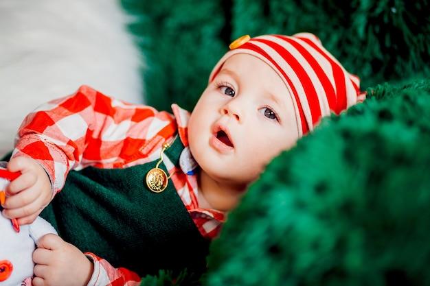 Charmant klein kind in rode plaid shirt en kerstmuts ligt op groene fauteuil