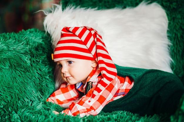 Charmant klein kind in rood geruite shirt en kerstmuts