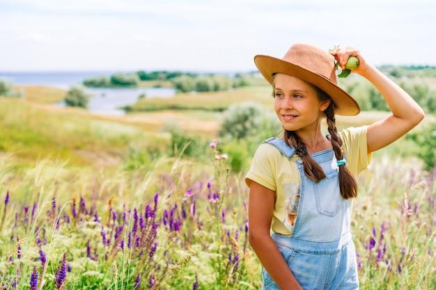 Charmant klein meisje dat in hoed appels in hand houdt tegen een schilderachtig heuvelachtig landschap