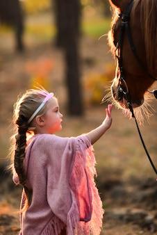 Charmant klein meisje gekleed als een prinses staat met een paard in de herfst bos