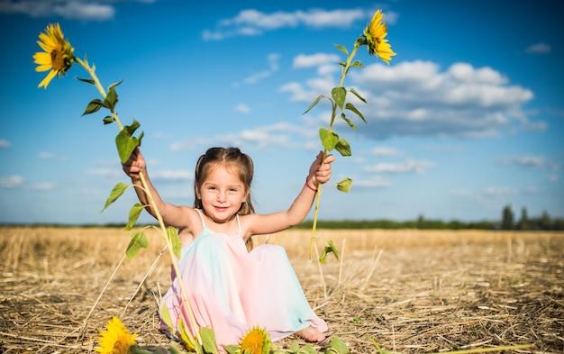 Charmant klein meisje in een lange zomerjurk zit op een veld op de achtergrond van een blauwe lucht en witte wolken