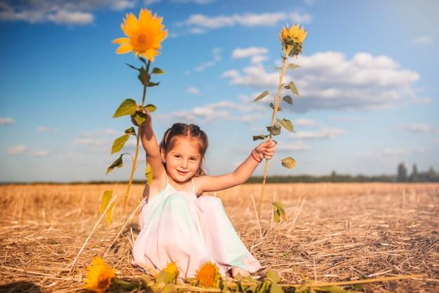 Charmant klein meisje in een lange zomerjurk zit op een veld