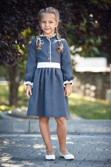 Charmant klein meisje in een retro jurk wandelen in de stad op een zonnige zomerdag. klein meisje draagt schooluniform. basisschoolmeisje met lang haar. studie en onderwijs.