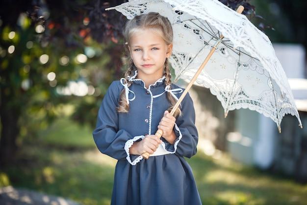 Charmant klein meisje in een retro jurk wandelen in de stad op een zonnige zomerdag