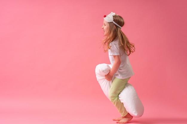 Charmant klein meisje in een slaapmasker en pyjama springt en vliegt op kussens