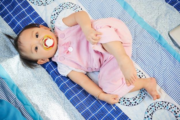 Charmant klein meisje in lichtroze overall liggend op bed en zuigen op fopspeen, uitzicht vanaf de top