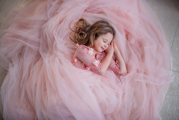 Charmant klein meisje in roze jurk ziet er mooi uit terwijl ze op de vloer slaapt