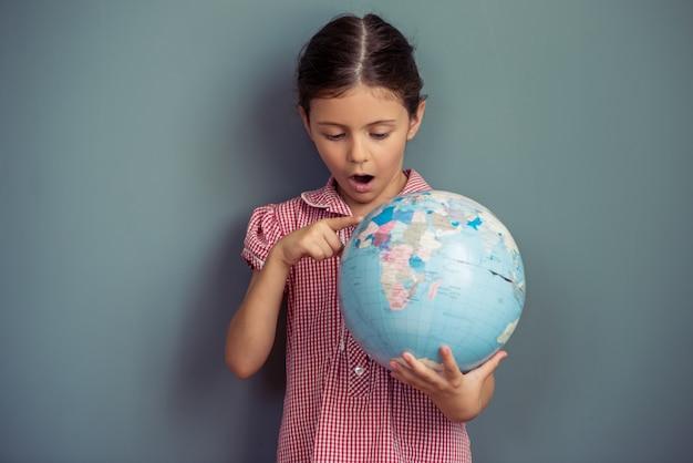 Charmant klein meisje in schattige jurk houdt een wereldbol