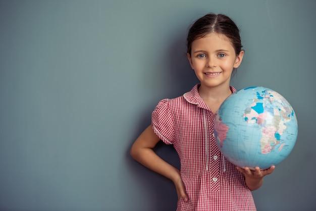 Charmant klein meisje in schattige jurk houdt een wereldbol.