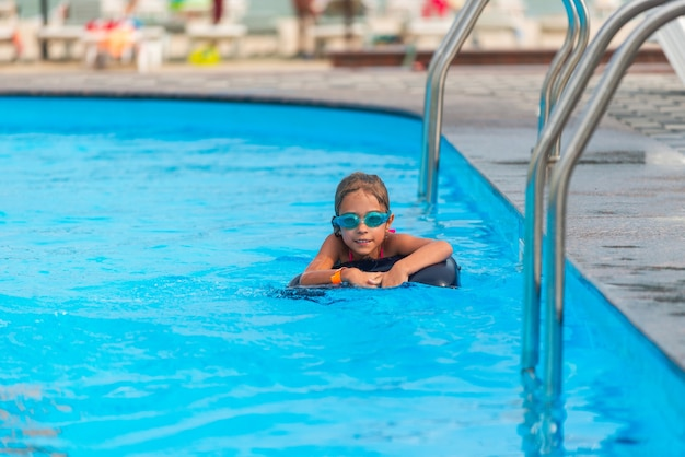 Charmant klein meisje in zwembril en een reddingsboei zwemt in het heldere blauwe water van het zwembad tijdens de zomervakantie. concept van kindervakanties