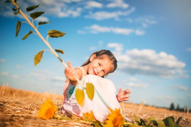 Charmant klein meisje met een zonnebloem in de hand zittend op het veld op een warme zonnige zomerdag