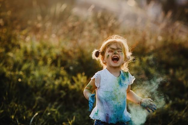 Charmant klein meisje met wit shirt bedekt met verschillende verven