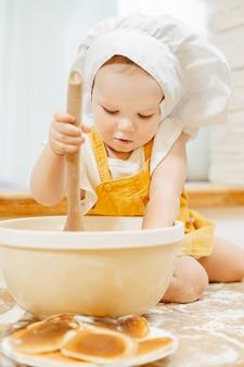 Charmant klein meisje van anderhalf jaar in een pak van kok roert deeg voor pannenkoeken in de kom
