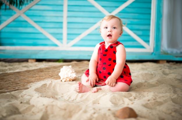 Charmant klein nieuwsgierig meisje in een bolletjesjurk zit op het zand tegen de achtergrond van een blauw landhuis.