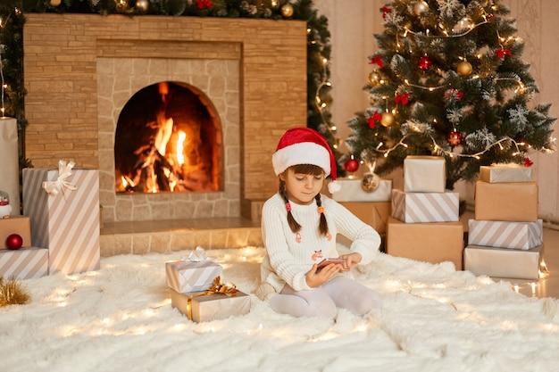 Charmant meisje communiceert via de telefoon met familieleden via een videogesprek en bedankt hen voor geschenken