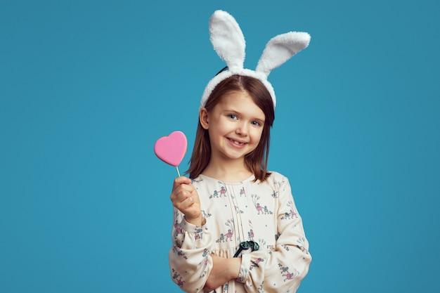 Charmant meisje dat een koekje in vorm van hart houdt dat konijntjesoren draagt