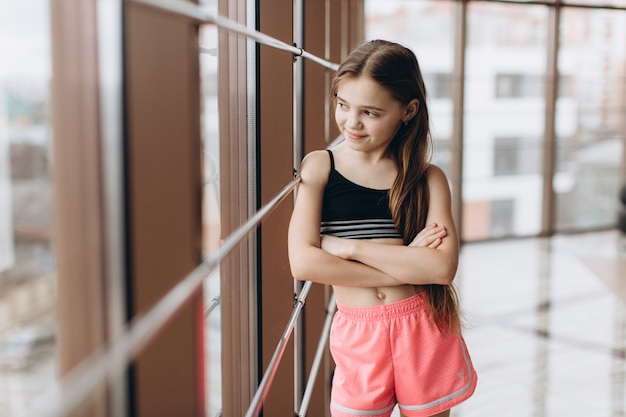 Charmant meisje dat het venster na yogaoefeningen kijkt in geschiktheidszaal