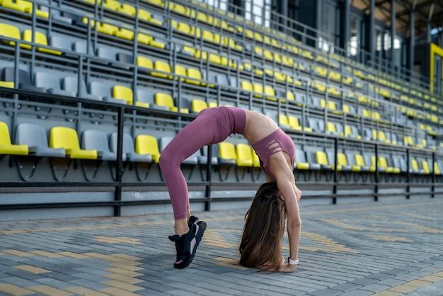 Charmant meisje doet rekoefeningen op tribunes van stadion voor perfect lichaam, zonnige zomerdag