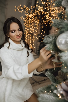 Charmant meisje hangt een stuk speelgoed aan een kerstboom