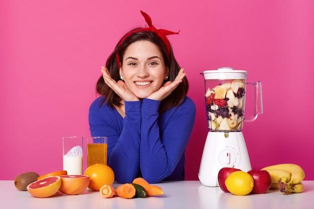 Charmant meisje, houdt handen onder de kin, draagt rode hoofdband, blauwe trui, gebruikt keukenmachine voor het maken van verse smoothie voor ontbijt, verschillende soorten fruit en groenten. dieet, gezond eten concept.