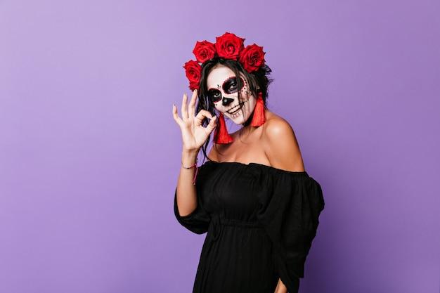 Charmant meisje in beeld van skelet dat gelukkig stelt. portret van leuke dame in zwarte bovenkant met rode rozen in krullen die ok tonen