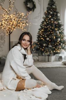 Charmant meisje in een gebreide jurk heeft een dromerige uitstraling en zit op de achtergrond van een kerstboom
