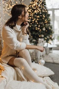 Charmant meisje in een gebreide jurk heeft een kerstspeelgoed en kijkt opzij