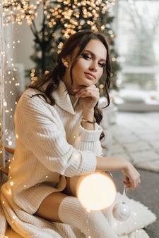 Charmant meisje in een gebreide jurk houdt een kerstspeelgoed vast en heeft een dromerige uitstraling
