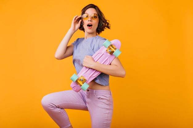 Charmant meisje in geel-gekleurde glazen poseren met verbaasde gezichtsuitdrukking. binnenfoto van spectaculair vrouwelijk model met roze skateboard.