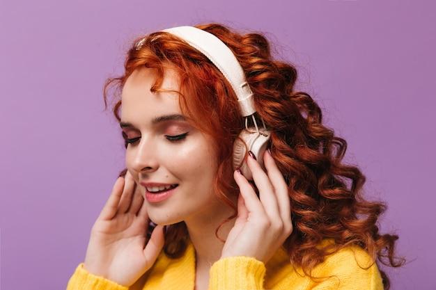 Charmant meisje in gele outfit zet een koptelefoon op en luistert naar muziek op geïsoleerde muur