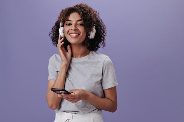 Charmant meisje in licht t-shirt luistert naar muziek en houdt telefoon vast