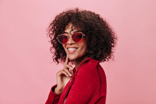 Charmant meisje in rode jas en heldere bril lacht op roze muur