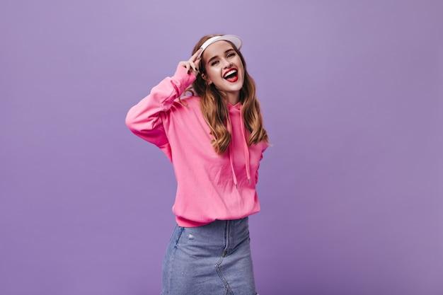 Charmant meisje in stijlvolle straatoutfit die lacht op paarse muur
