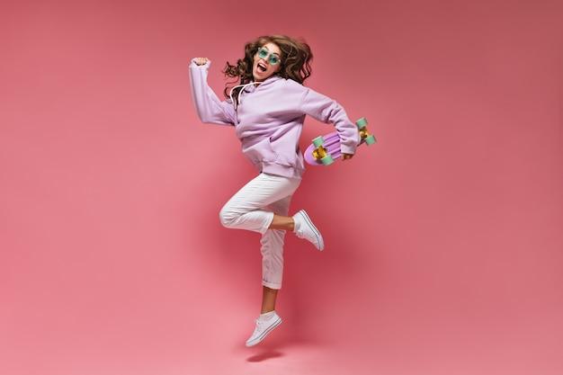 Charmant meisje in witte broek en oversized paarse hoodie springt op geïsoleerde roze muur