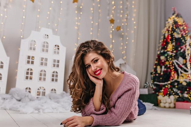 Charmant meisje liggend op wit tapijt en poseren tegen kerstboom
