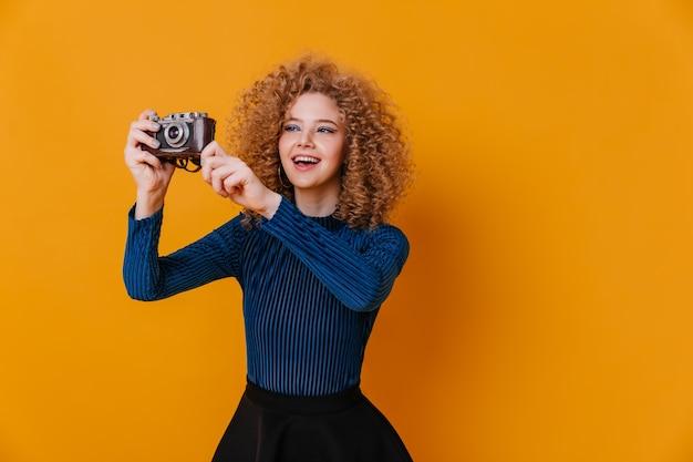 Charmant meisje met blonde krullen maakt foto op retro camera. vrouw draagt blauwe blouse op gele ruimte.