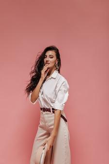 Charmant meisje met krullend donker haar in gouden oorbellen, witte blouse, beige broek met bruine riem op zoek naar camera op roze muur